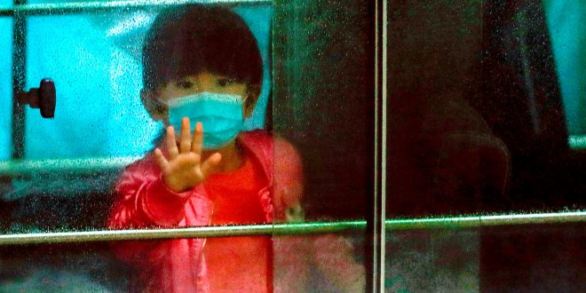 A child waves as she sits in a vehicle carrying residents evacuated from a public housing building, following the outbreak of the novel coronavirus, outside Hong Mei House, at Cheung Hong Estate in Hong Kong, China February 11, 2020. REUTERS/Tyrone Siu     TPX IMAGES OF THE DAY